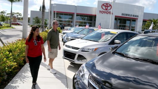 A salesperson (left) shows vehicles to a shopper at a Toyota dealership.